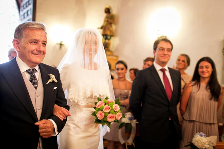 Novia entrado en la iglesia del brazo de su padre. Fotos de bodas