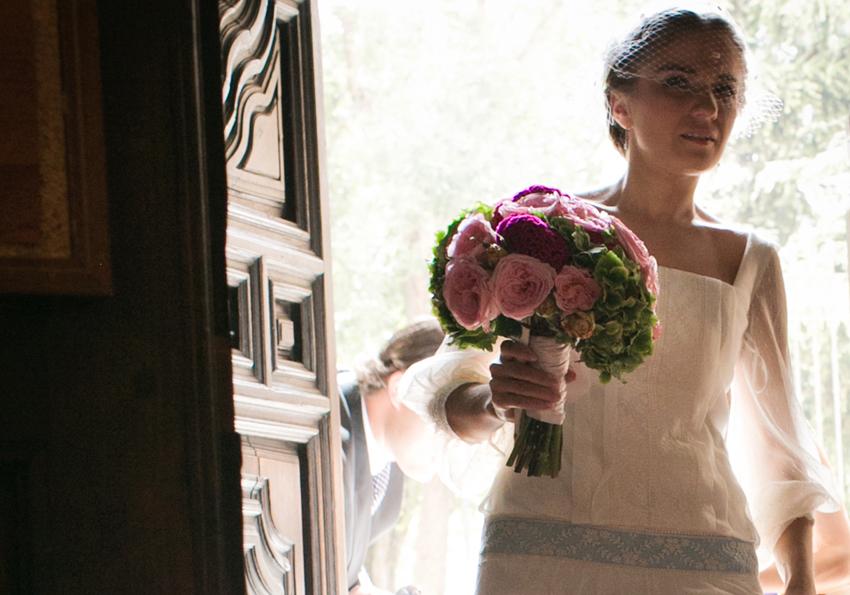 Novia entrando en la iglesia con el ramo en la mano, fotos de bodas