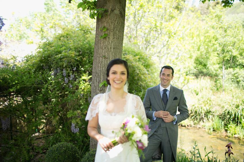 Imagen de los novios con detalle del novio en segundo plano, fotos de bodas