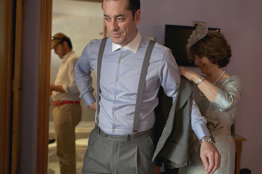 La madre ayuda a ponerse la chaqueta al novio. Reportajes de boda en Madrid