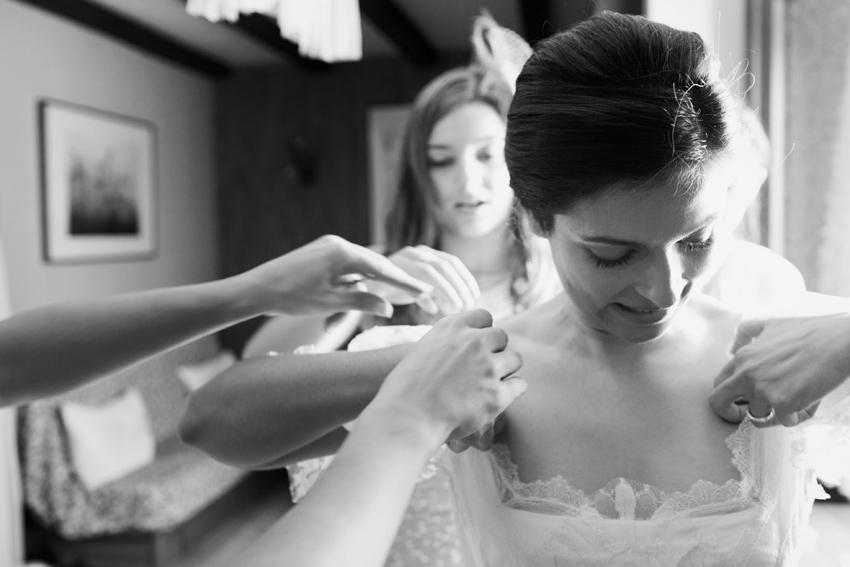 Ayudando a la novia a colocarse el vestido, fotos artísticas de bodas