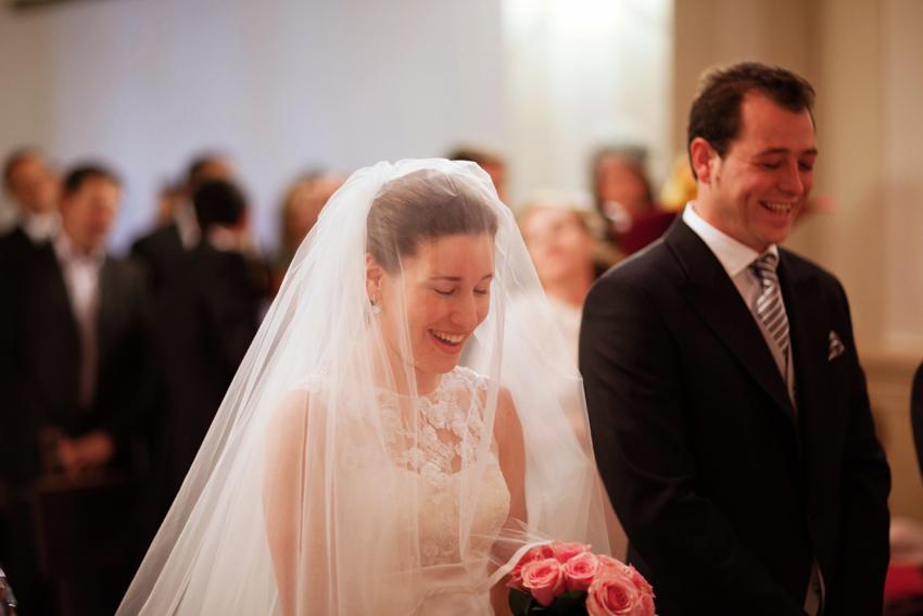 Los novios sonrientes delante del altar, fotógrafo de bodas en Ciudad Real