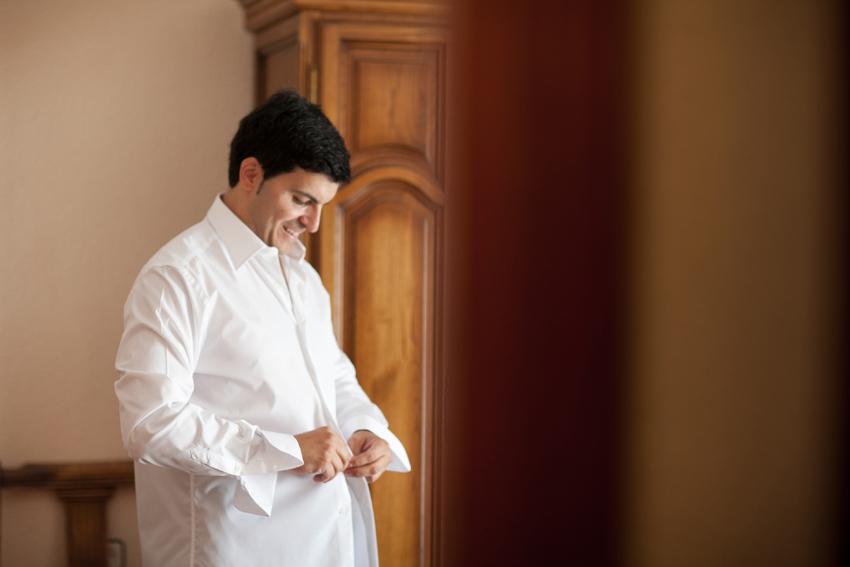 Foto del novio abrochándose la camisa, fotógrafo de bodas en Ciudad Real