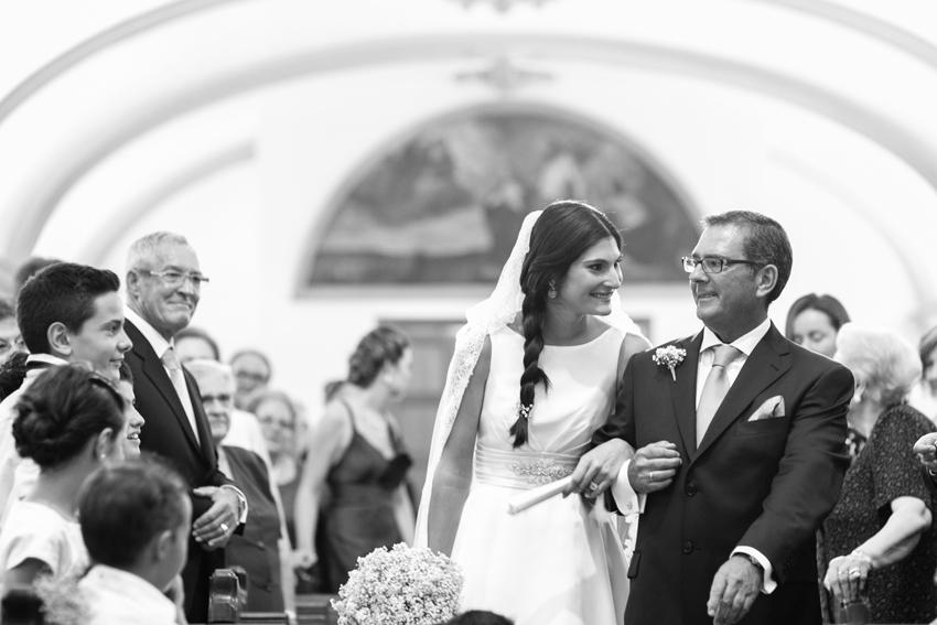 La novia dentro de la iglesia, acompañada por su padre, fotos de bodas