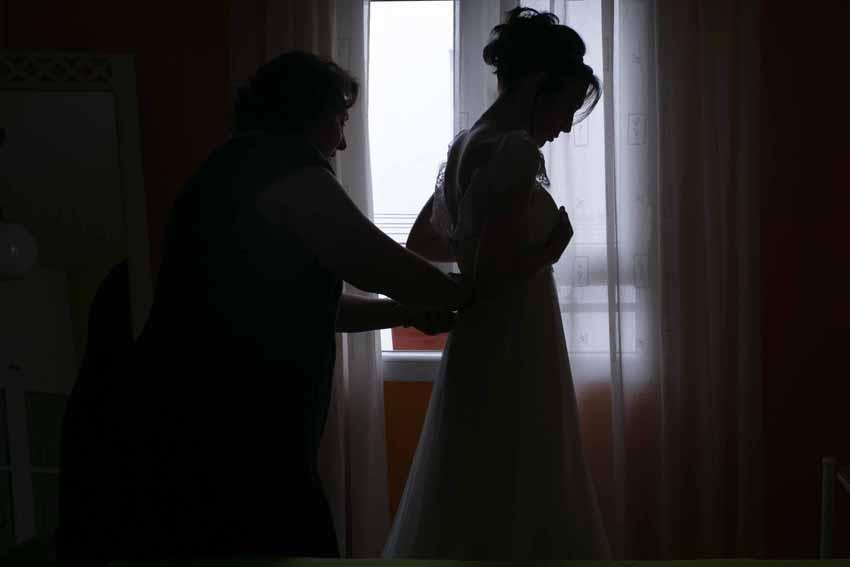 Madre ayudando a la novia a ponerse el vestido. Fotos artísticas de bodas