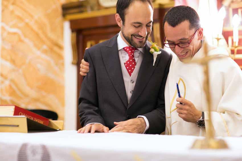 El sacerdote y el novio sonrien en un momento de la ceremonia