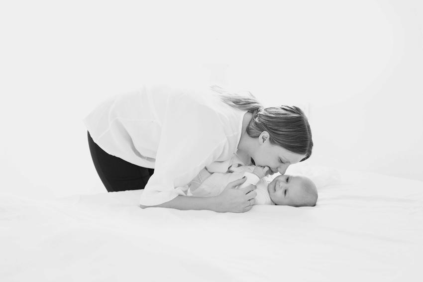 Madre con su bebé en la cama. Fotos artísticas de familia