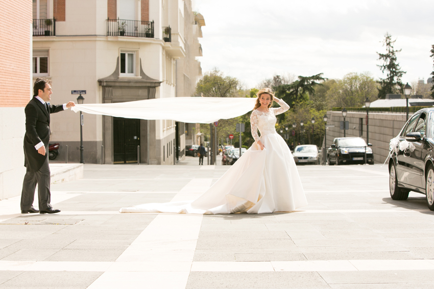 El novio sjeta el velo de la novia. Fotos artísticas de bodas