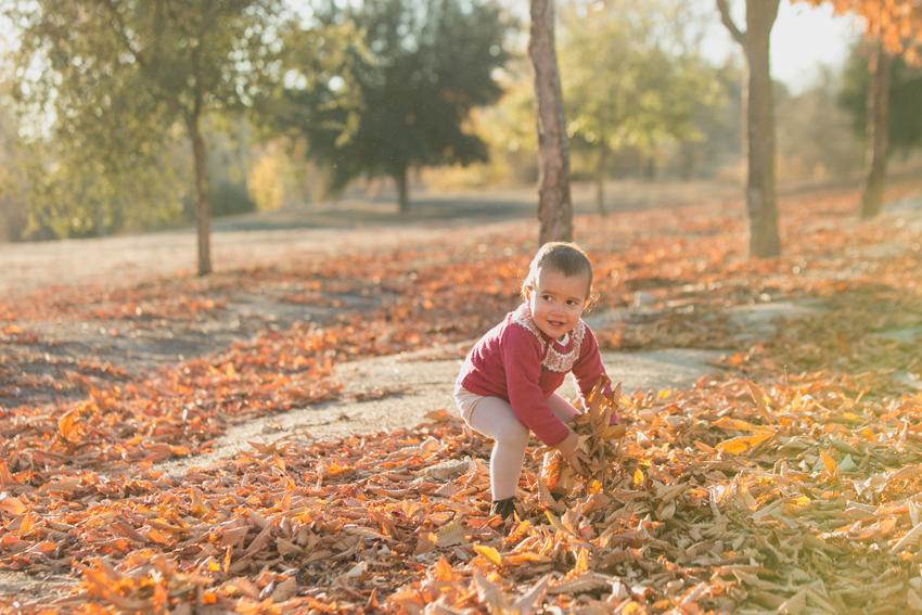 El más pequeño jugando con las hojas. Fotógrafo infantil en Madrid