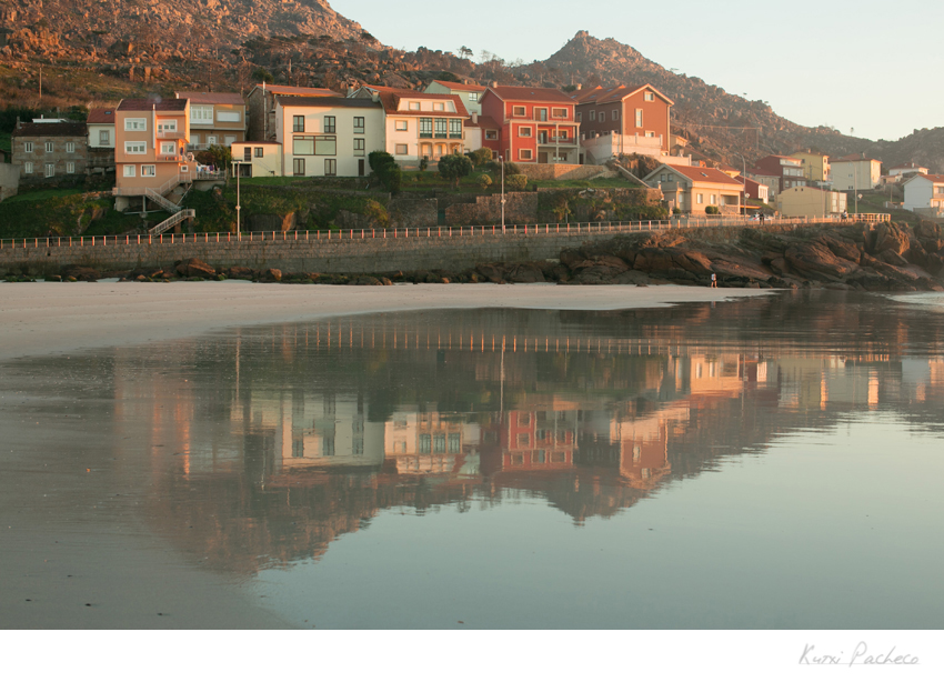 Edificios reflejados en el agua. Reportaje de la Costa de la Muerte