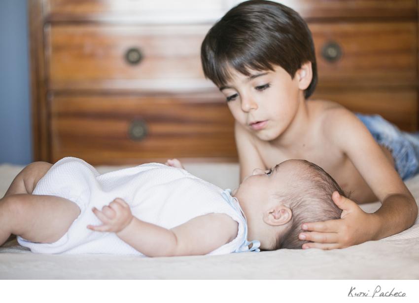 Álvaro acaricia a su hermano pequeño. Sesión infantil en Madrid